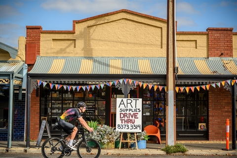 Bike riding past art shop with sign saying open for drive through