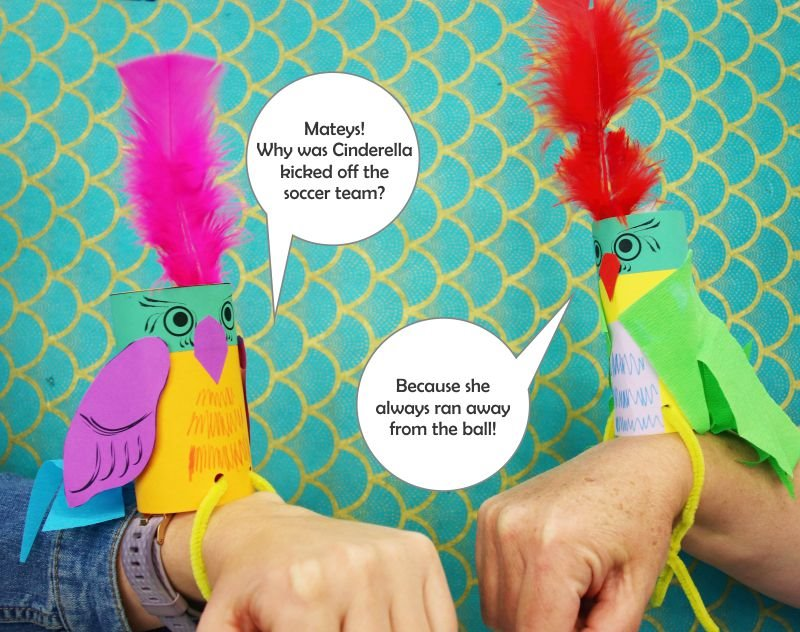 Kids craft example of two parrots made from coloured cardboard and paper, sitting on arms