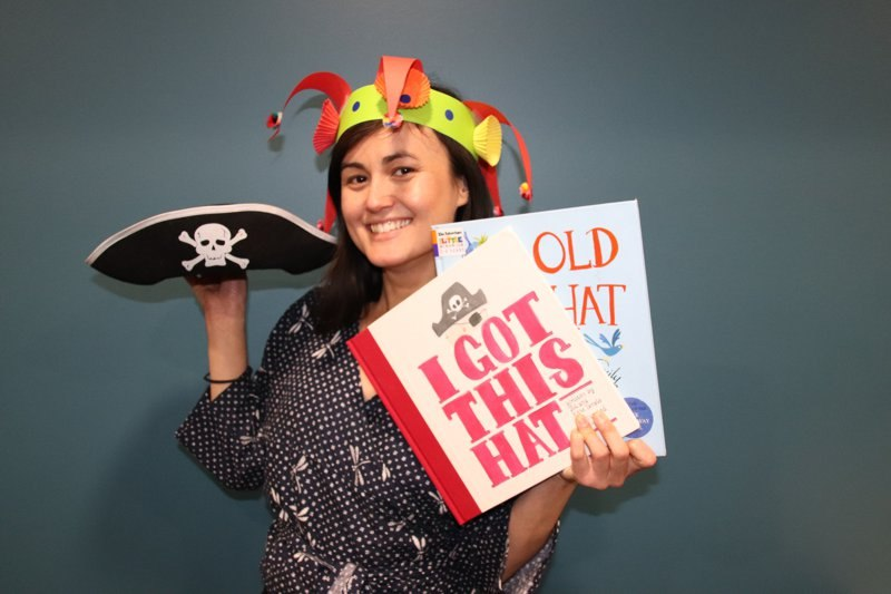 Library staff member holding books, pirate hat and wearing an example of the jester hat craft