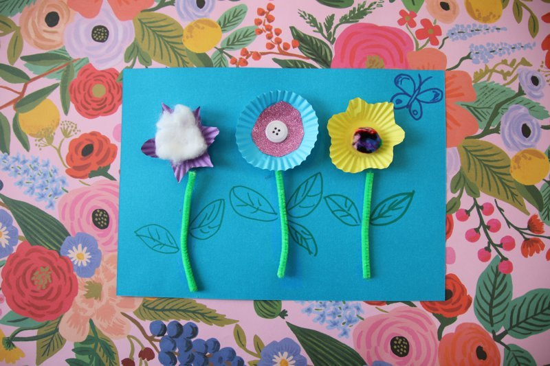 Flower craft made of cardboard, patty pans, pipecleaner, buttons and pompoms.