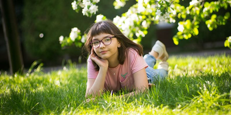 Young teen book club cover image teenager lying on the grass